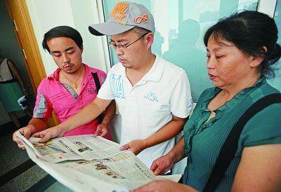 昨日,刘洋(左)、刘培(中)和母亲戴亚兰(右)阅读本报相关报道。
